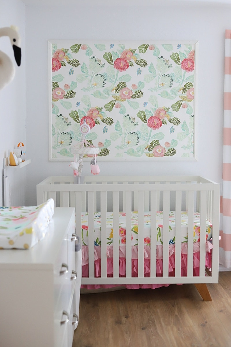baby girl nursery with floral crib bedding and nursery wallpaper above the crib that has watercolor flowers