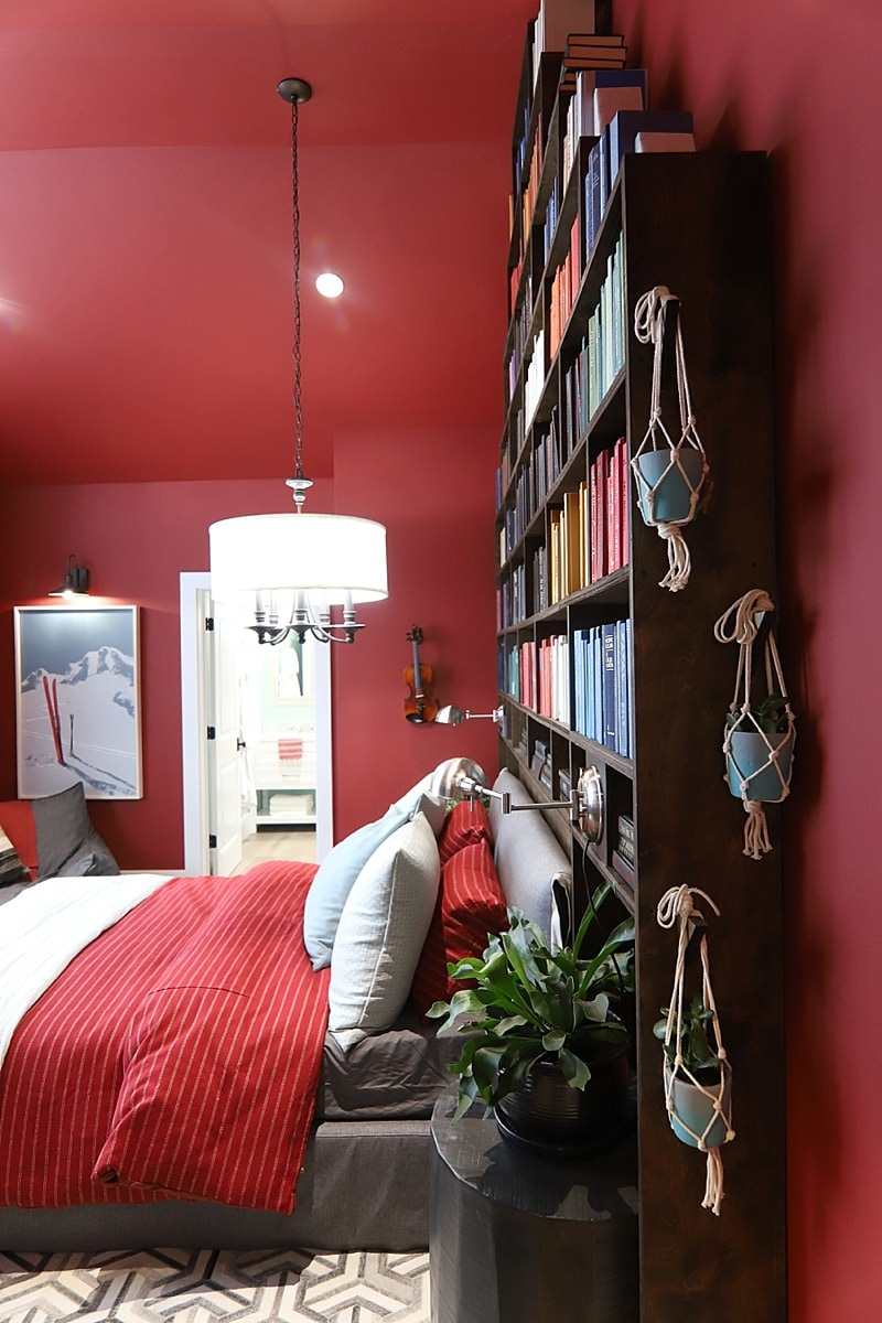 Bedroom with red ceiling and walls with a massive bookshelf as a headboard