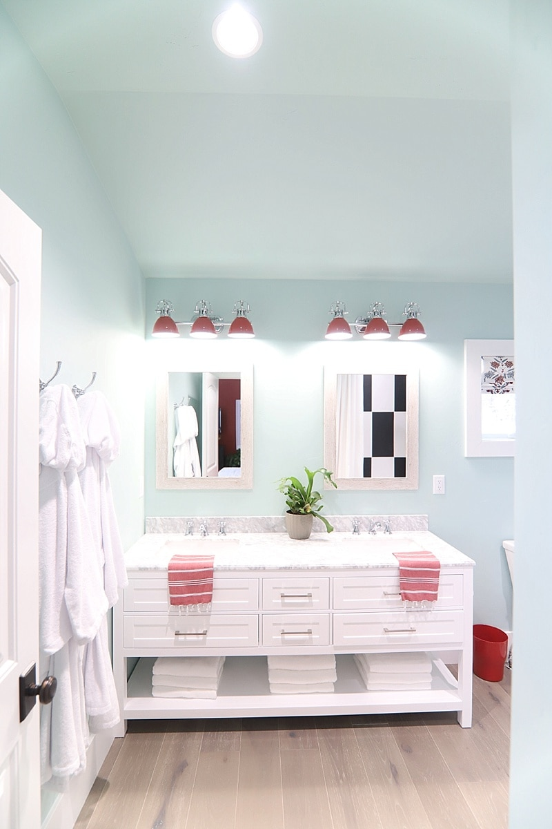 Master bathroom thats mint blue with white cabinets and marble countertops