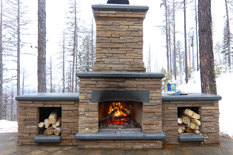 Outdoor fireplace with logs and snowy background