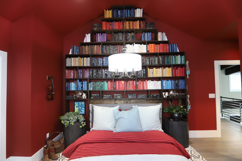 Red bedroom with white trim and a floor to ceiling bookshelf as headboard