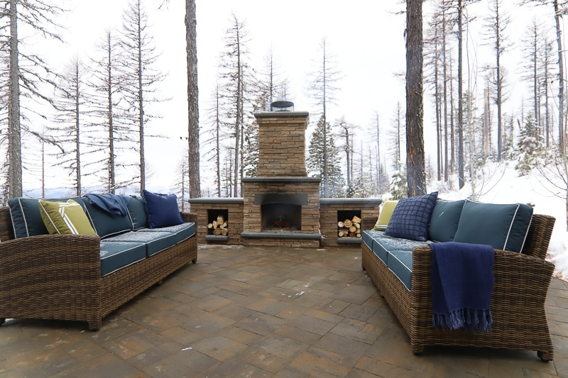 Stoned patio with outdoor fireplace with snow