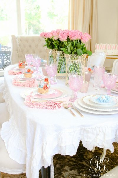 A decorated Easter table with pink roses in the middle and DIY mini Easter baskets on each plate.