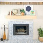 Fireplace makeover with venetian plaster and blue patterned tile, with a floating wood mantle.