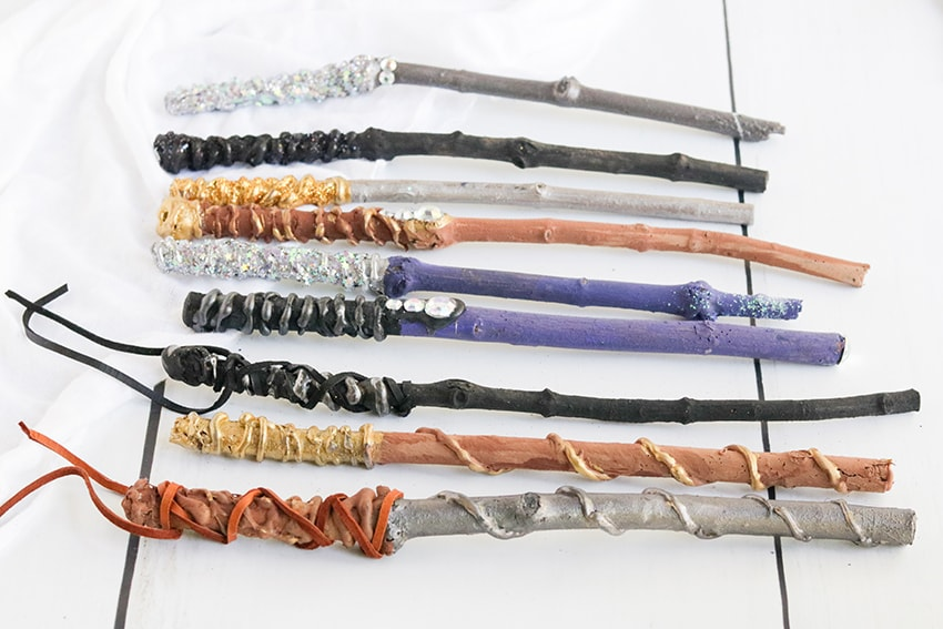 DIY Harry Potter wands with sticks covered in paint, glitter, hot glue and other craft supplies.