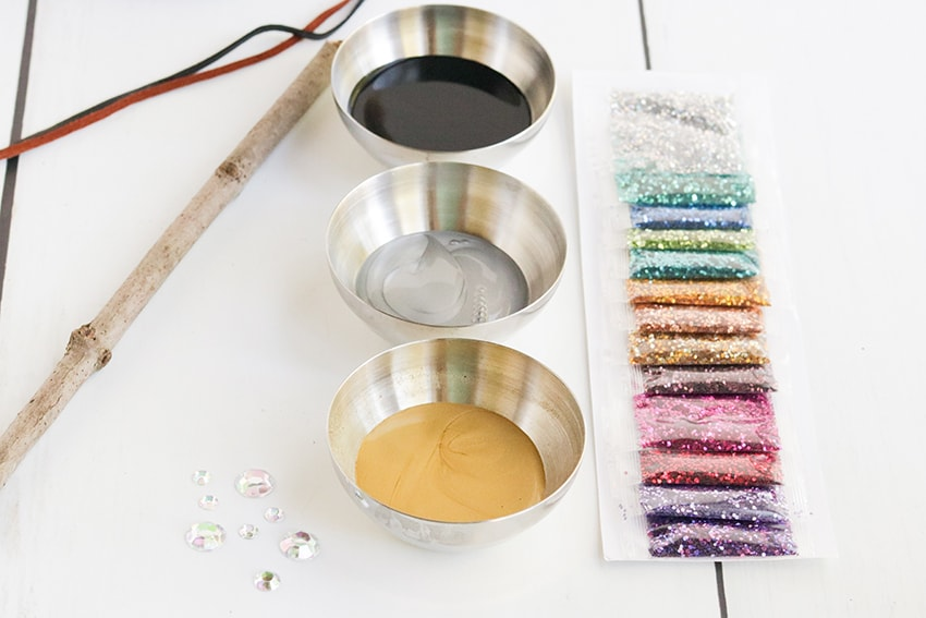 Supplies needed for diy harry potter wand such as hot glue, paint, twine, gemstones, glitter and sticks