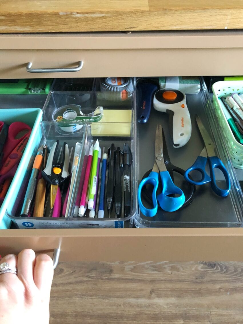 Shallow drawer filled with organized supplies in a craft room.