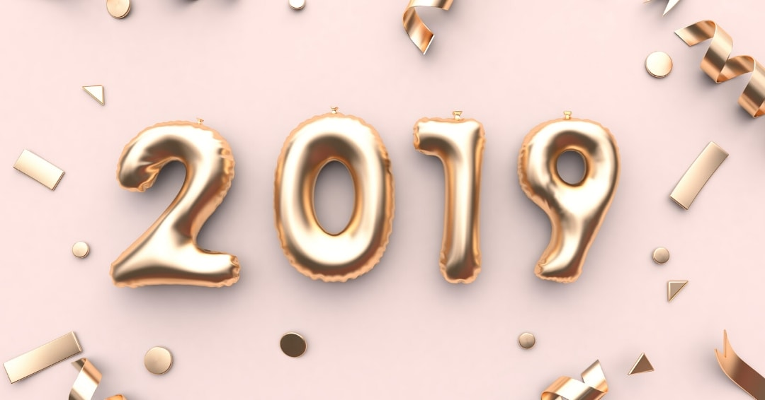 the numbers 2019 on a pink background with gold confetti