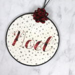 Round ornament made from an embroidery hoop with plaid noel lettered on it.