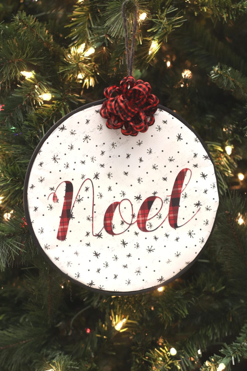 Noel ornament made on a cricut hanging on a christmas tree.