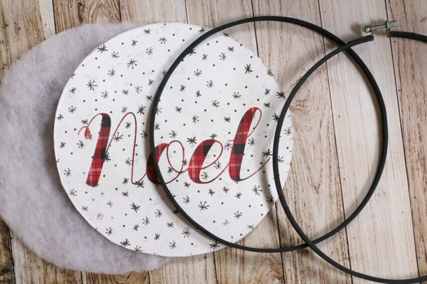 Black embroidery hoop with fabric circle that says noel on it and round batting.
