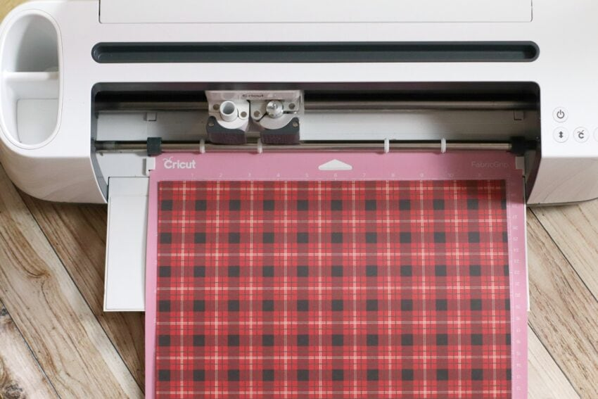 Cricut machine with plaid paper loaded in it.