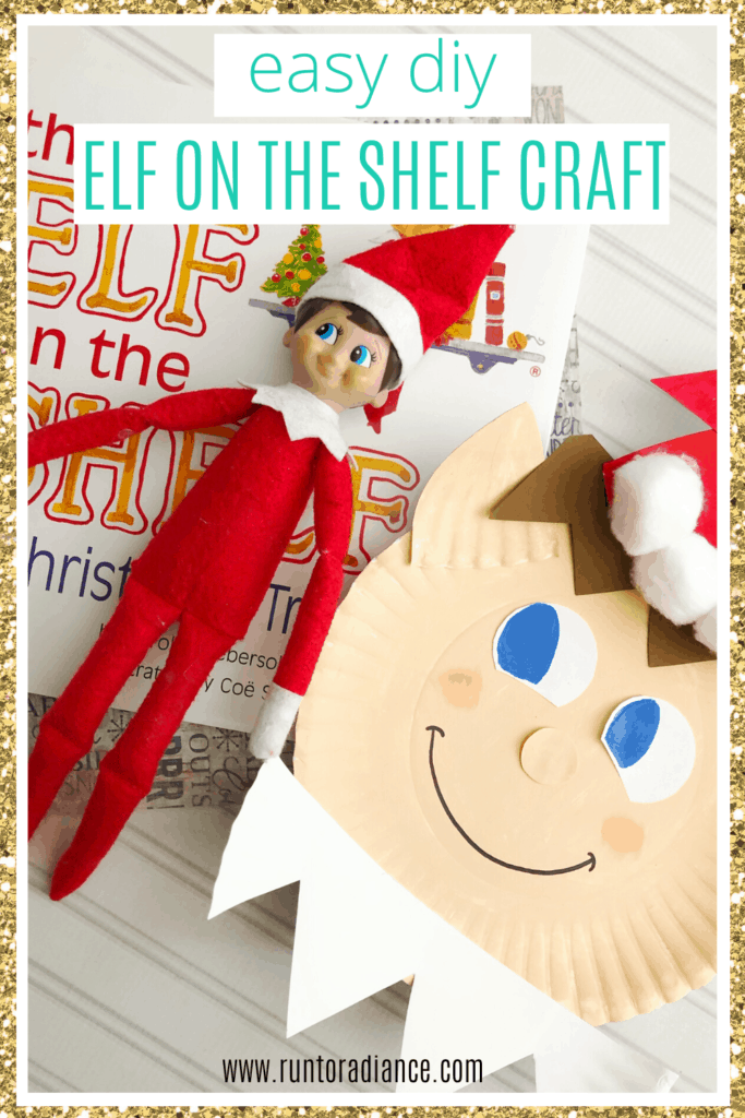Elf on the shelf lying next to a paper plate craft of his face.