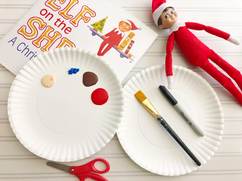 Elf on the shelf laying next to a paper plate with paint in preparation for a craft project.