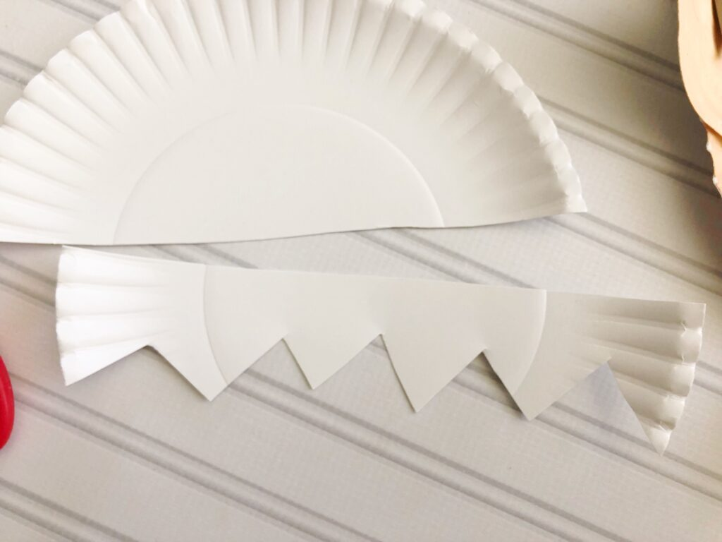 Visual of how to cut a paper plate to create an elf on the shelf craft.