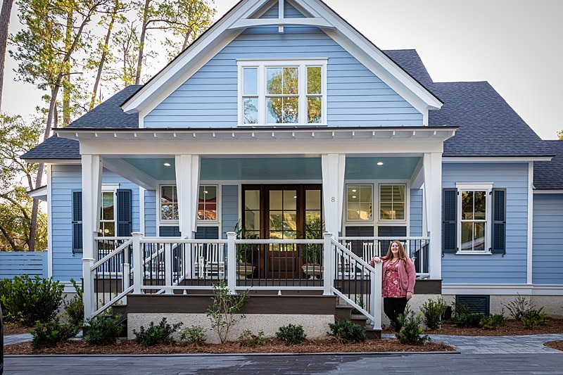 HGTV Dream Home 2020 - blue house with large front porch and a woman standing in front.