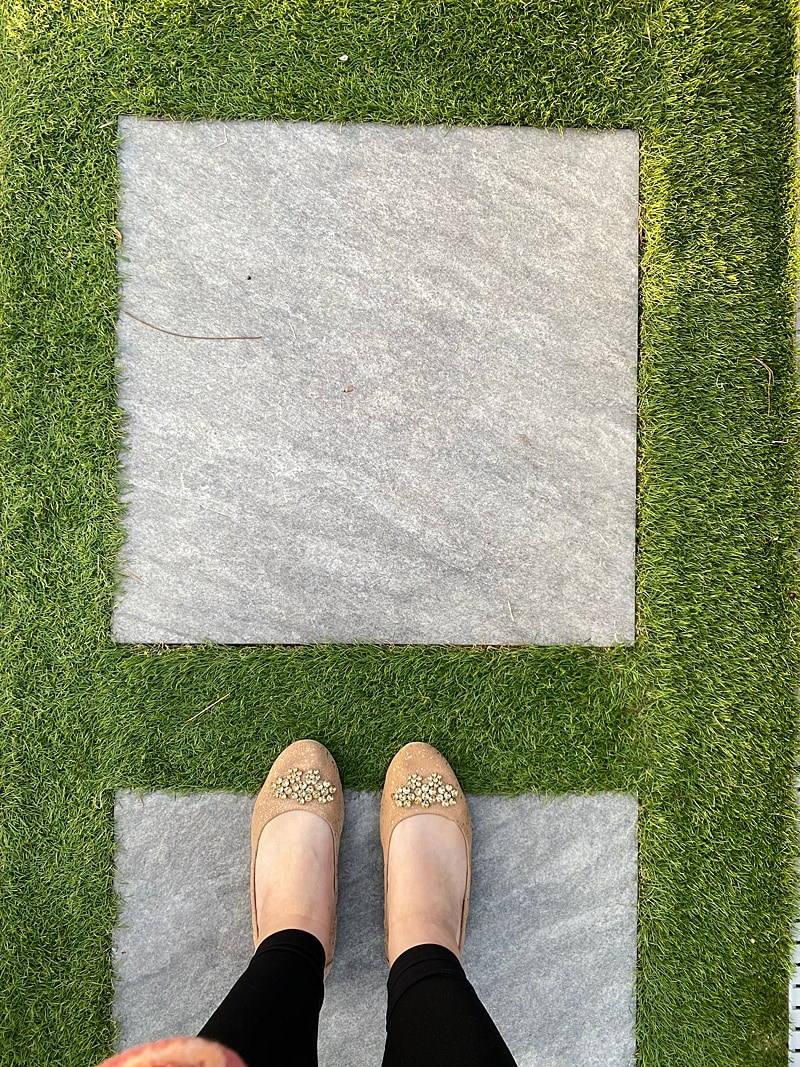 Woman standing on large pavers with pre-cut turf that fit together