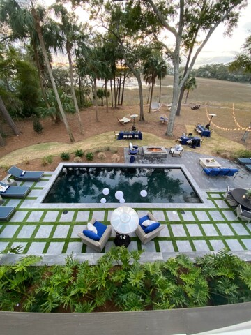 Overhead shot of swimming pool with pavers and turf, with ocean in background