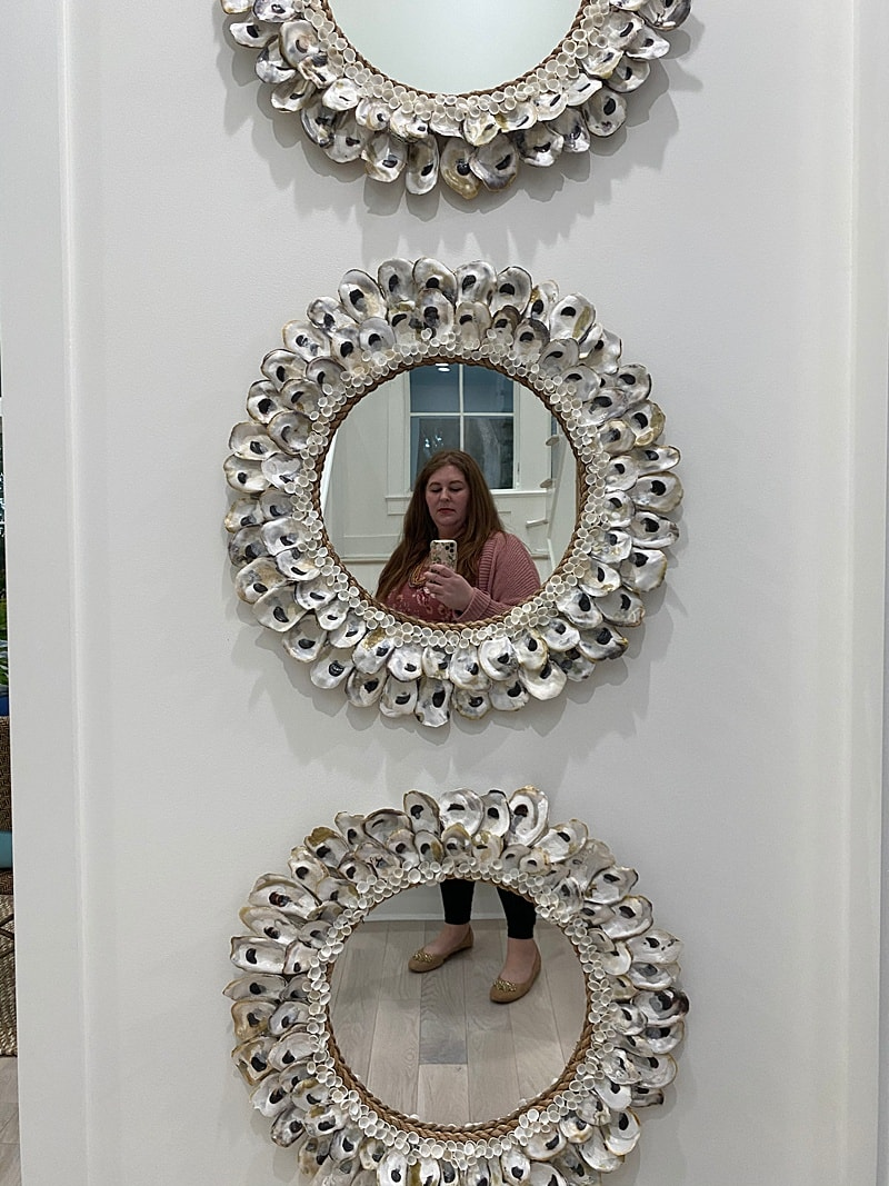 3 round mirrors with oyster shells covering each.