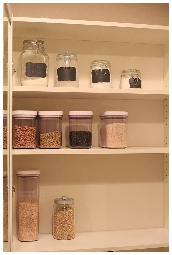Pantry shelves with mason jars and clear containers with rice, beans and pasta