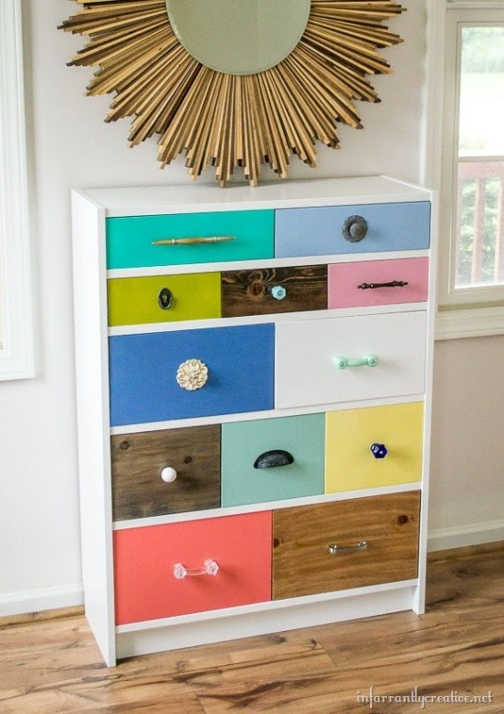White bookcase with colored drawers against a white wall with circular gold mirror