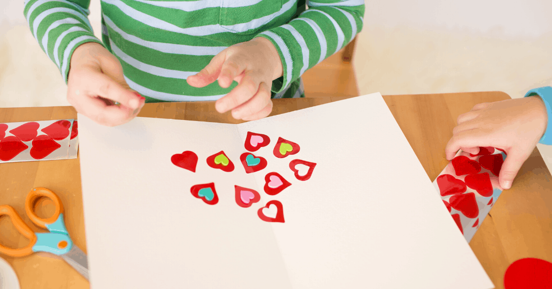 kids crafts with heart stickers on wooden kitchen table