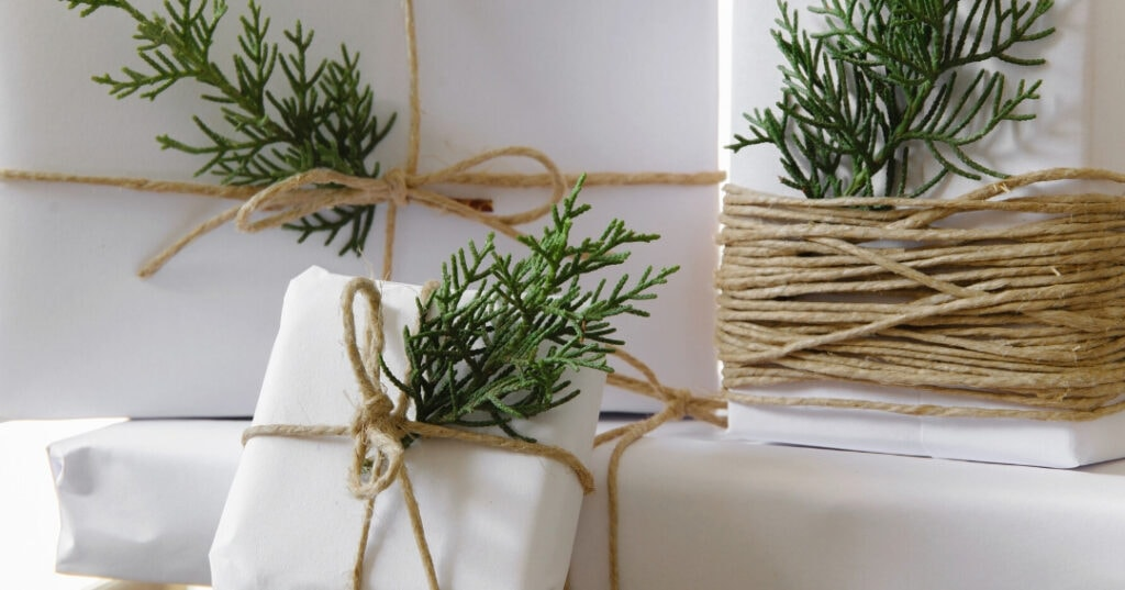 white paper wrapped gifts with brown twine and a green leaf