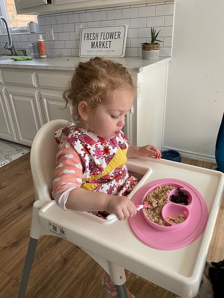 Toddler eating breakfast from their high chair