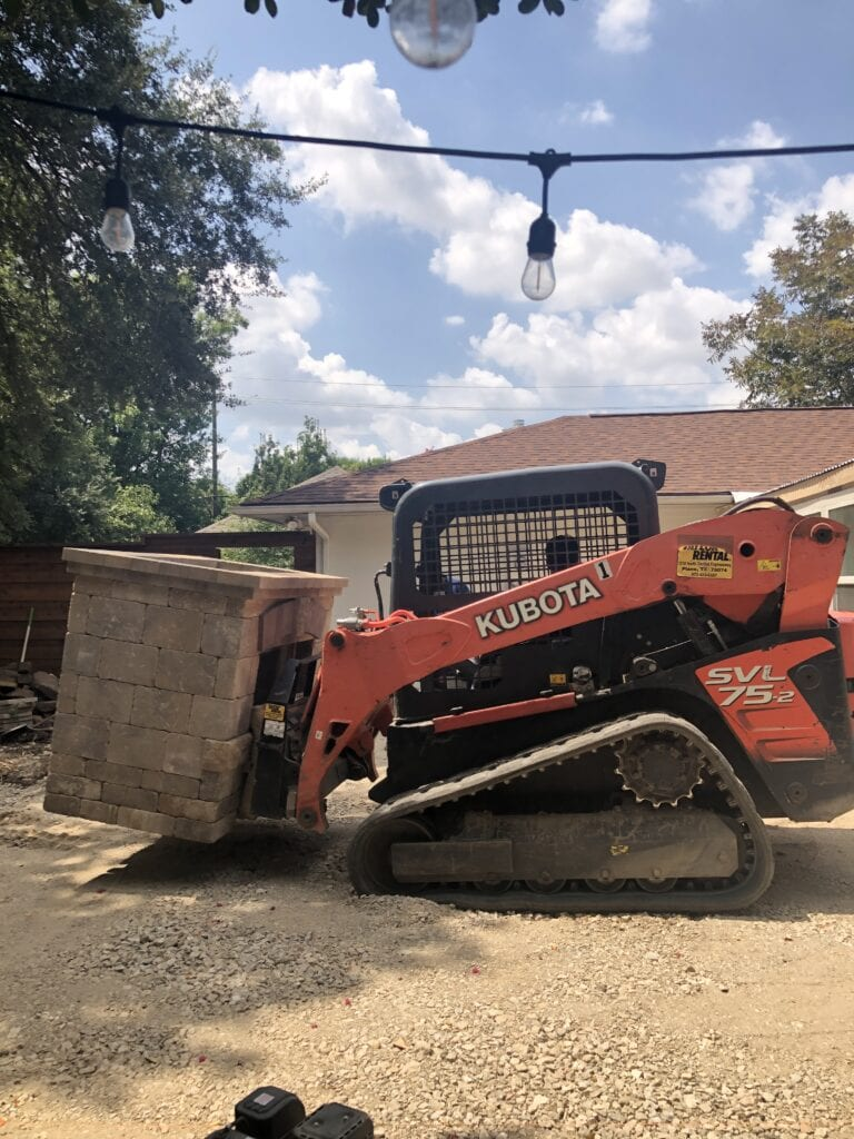 Forklift with stone fireplace in a backyard