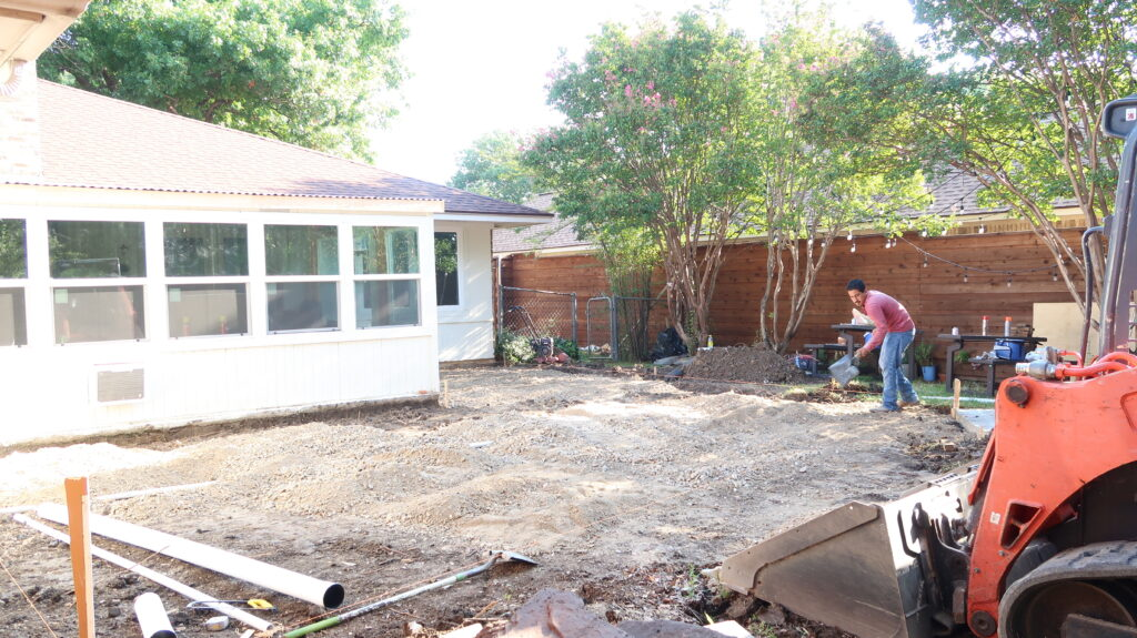 Man adding paver base to yard as he preps for pavers.