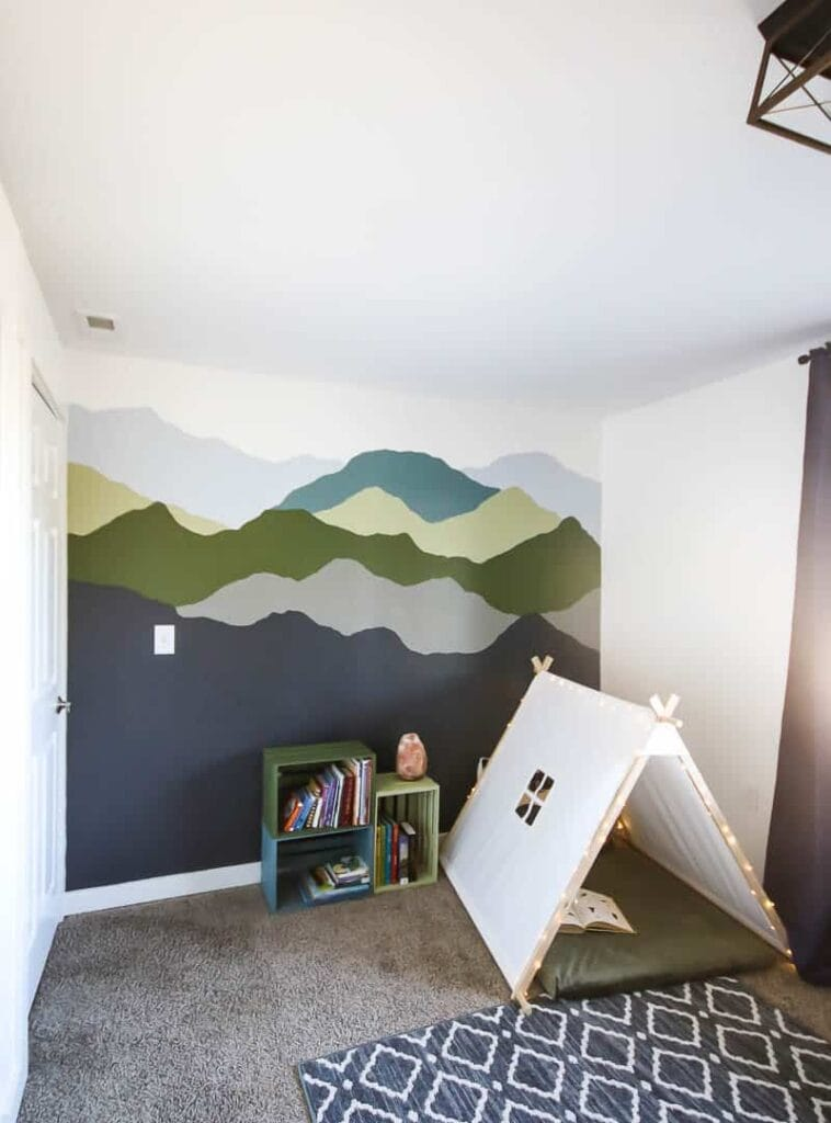 A toddler's room with a mountain mural accent wall