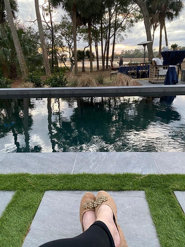 Woman with pink ballet flats has feet propped up in front of a swimming pool
