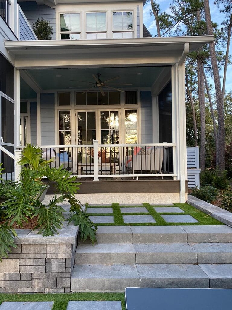 Blue home with a covered patio and green yard space