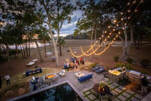 Aerial shot of a backyard with a pool, outdoor kitchen, outdoor dining, lounge area, and string lights