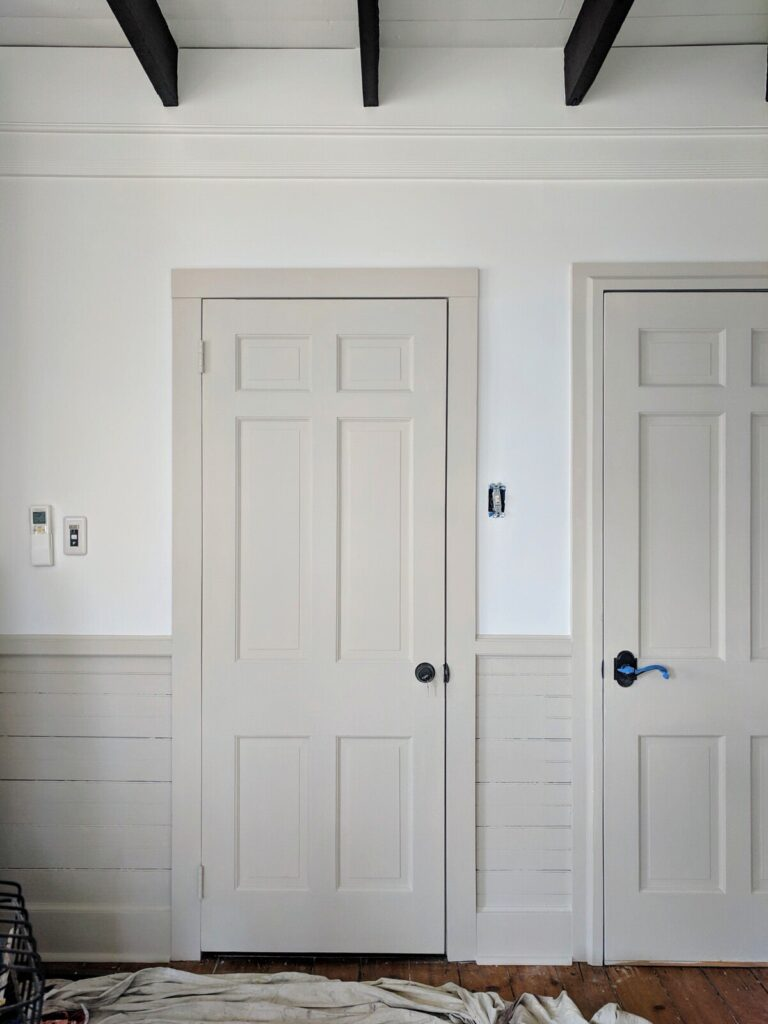 Hallway and interior doors with white walls and wainscotting and trim Baby Fawn by Benjamin Moore.
