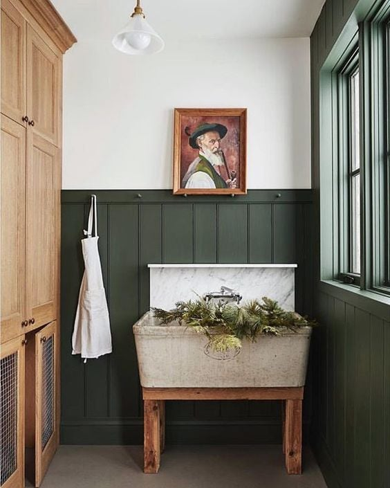 Rustic bathroom with vintage sink basin, wainscotting and trim painted in Backwoods by Benjamin Moore.
