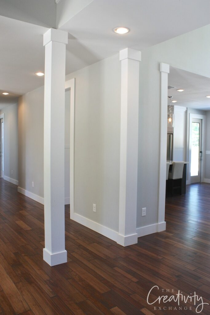 Hallway with pale gray walls and columns and trim color Decorator's White by Benjamin Moore.