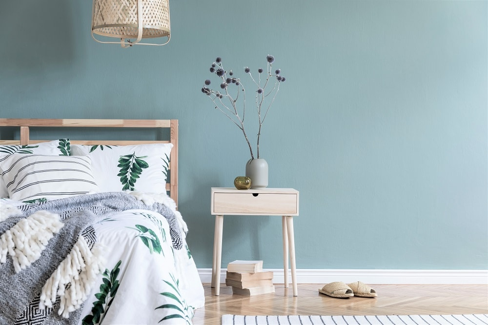 Guest bedroom with bed and bedside table and wall painted in Benjamin Moore Buxton Blue