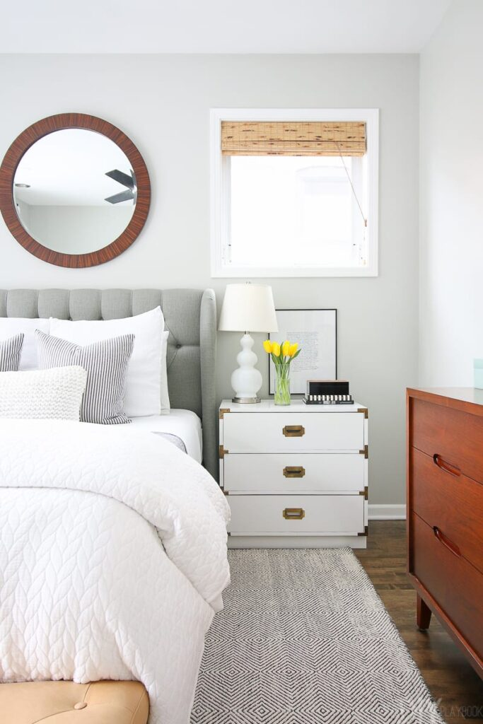 Guest bedroom with gray upholstered bed, circular mirror and walls painted with Benjamin Moore Gray Owl