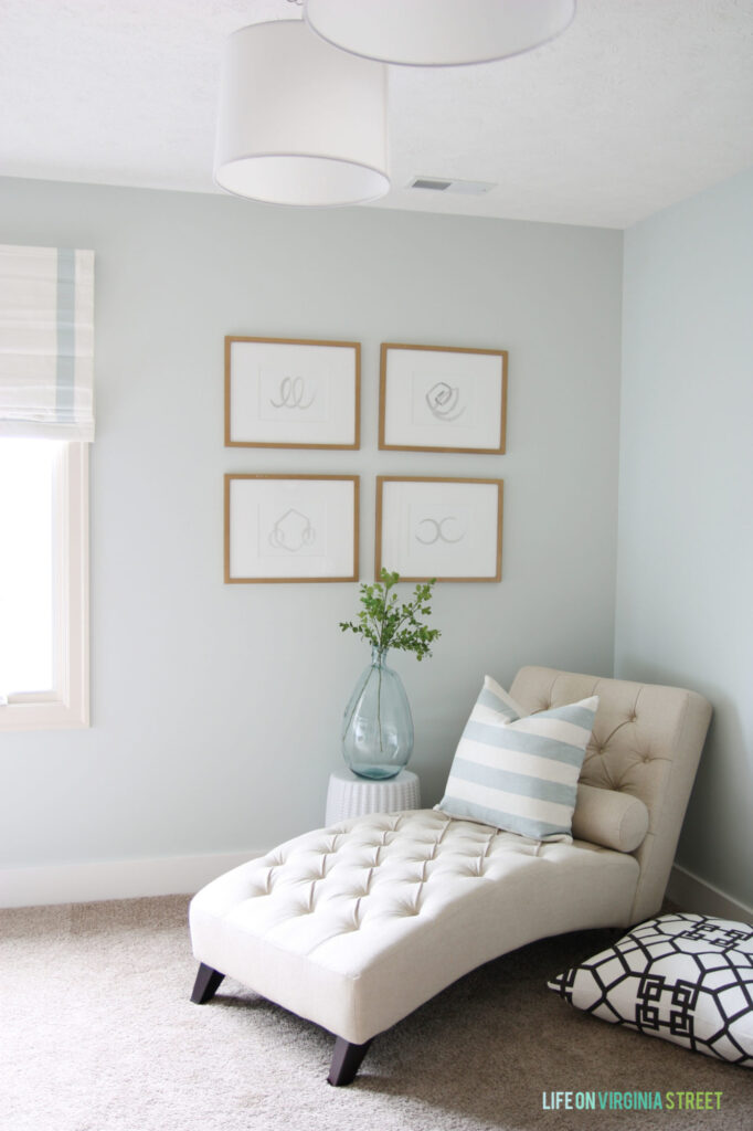 Corner of guest bedroom with chaise lounge and wall painted in Benjamin Moore Healing Aloe, and four gallery frames on the wall
