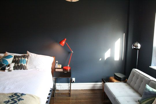 Guest bedroom with bright red orange table lamp on bedside table and walls painted in Benjamin Moore Mysterious