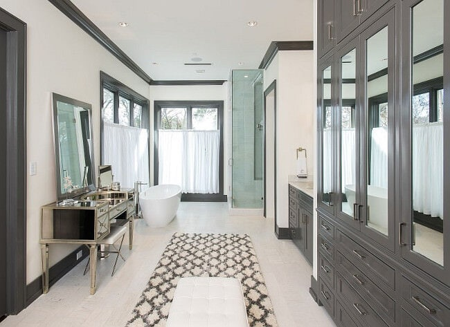 Long narrow bathroom with white walls, cabinets and trim color Kendall Charcoal by Benjamin Moore.