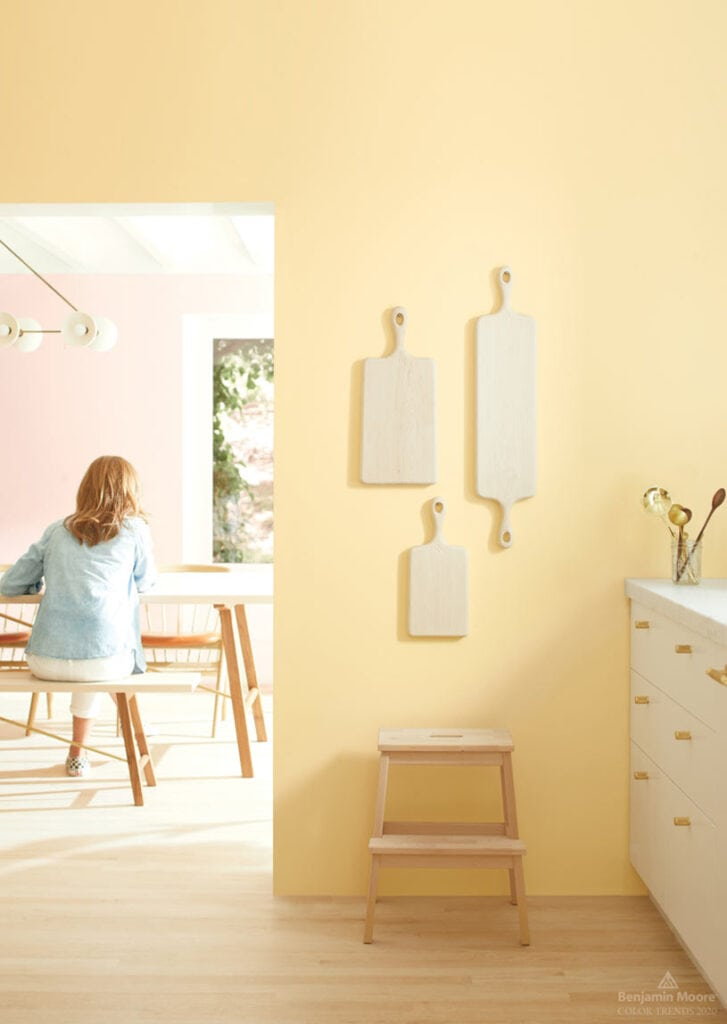 A kitchen doorway leading to a dining room with walls painted in Benjamin Moore Golden Straw and three cutting boards hanging on the wall