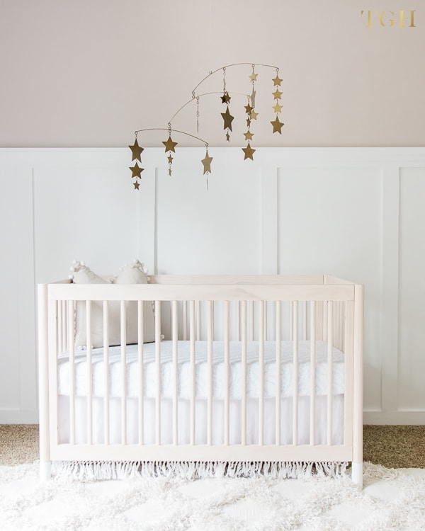 A nursery with a crib and star mobile against a half wall painted in Benjamin Moore Big Bend Beige and white wainscotting