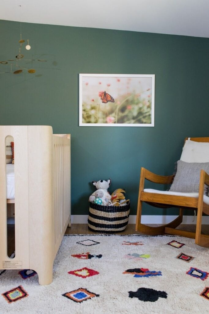 Nursery with crib and rocking chair and wall painted in Benjamin Moore Caldwell Green