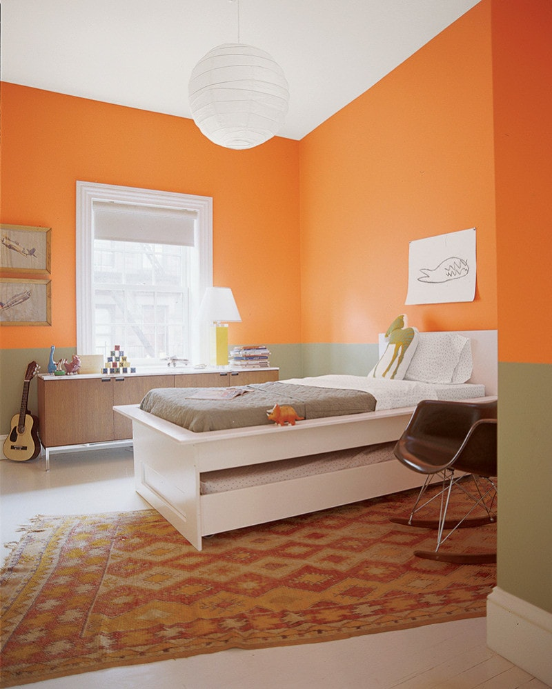 Kid's bedroom with a twin bed and guitar and half wall painted in Benjamin Moore Calypso Orange