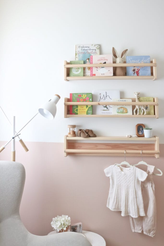 Nursery with half wall painted in Benjamin Moore Odessa Pink and Simply White. Bookshelves display children's books and baby girl clothes hang from a wall rod