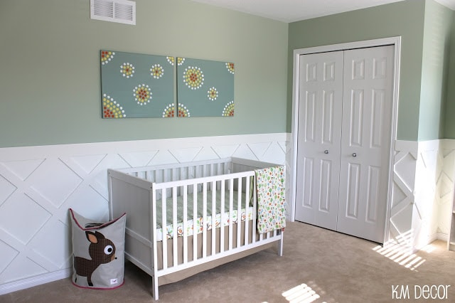 Nursery with half wall painted in Benjamin Moore Prescott Green and white wainscotting. A crib sits against the wall.