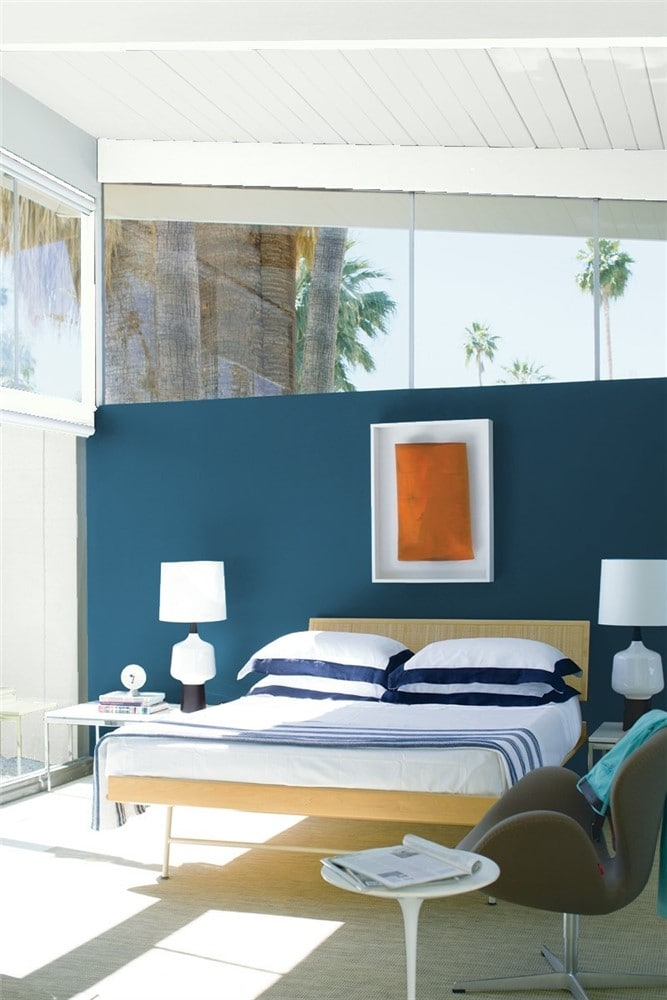 Mid-century modern styled master bedroom with accent wall painted in Benjamin Moore Blue Danube and angled window overhead, showing palm trees outside