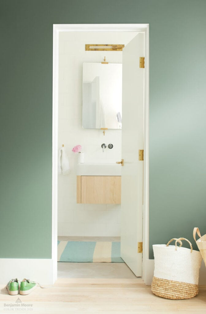 Master bedroom with walls painted in Benjamin Moore Cushing Green, a door opening into a master bathroom